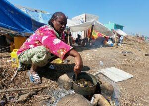 إثيوبية فرت من تيغراي تحضر الطعام على الحدود السودانية (رويترز)